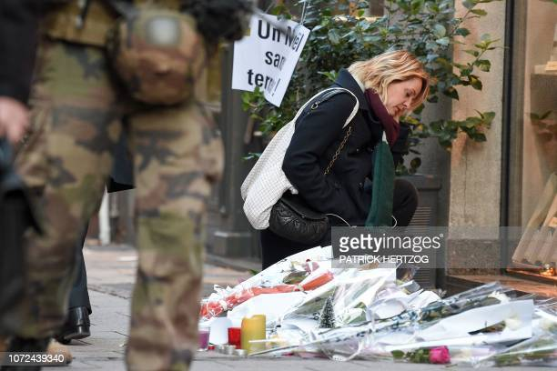 A woman is seen next to flowers and candles laid in the street in tribute to the victims of a deadly shooting two days ago in central Strasbourg on...