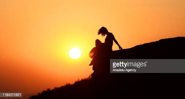 Woman is seen on a hill during sunset in Usak, Turkey on August 26, 2019.