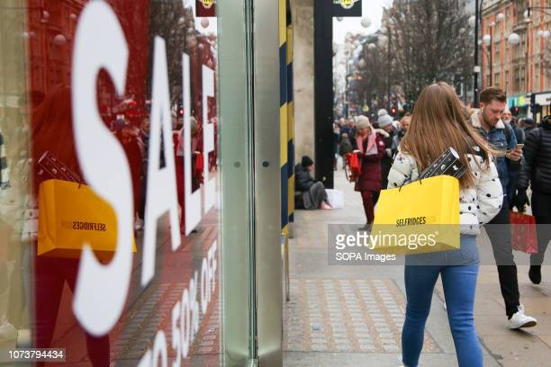 A woman is seen on London's Oxford Street with Selfridge's shopping bags with 9 days to Christmas Day Retailers are expecting a rush of shoppers in...