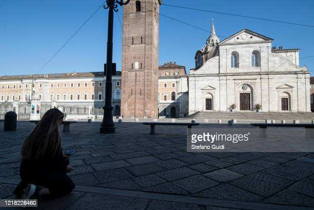 A woman is seen praying and watching a live stream in front of the Turin Cathedral to celebrate Easter Holy Saturday on April 11 2020 in Turin Italy...