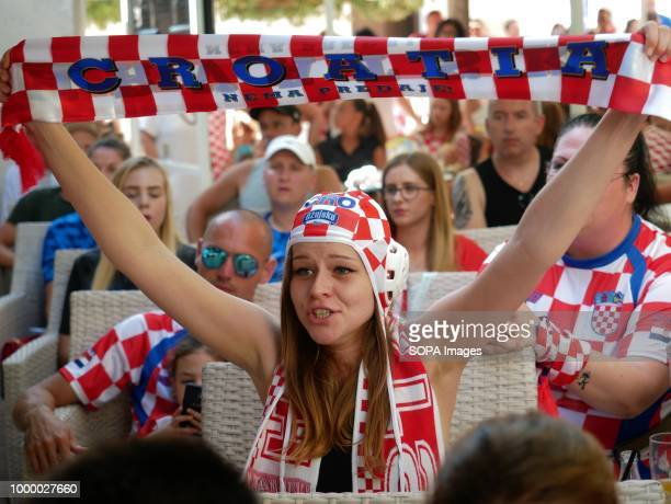 A woman is seen raising a Croatian banner Croatians in the Island of Pag watched the world cup football final match Croatia vs France Croatia lost 24...