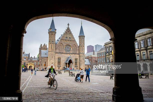 Woman is seen riding her bike at the Binnenhof on July 15, 2021 in The Hague, Netherlands. The Binnenhof is closed due to a lengthy renovation,...