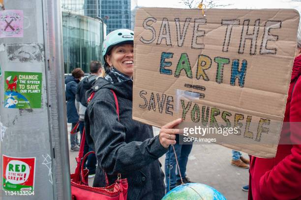 A woman is seen smiling while holding a placard during the demonstration Thousands of people gathered as always at the Brussels North station to...