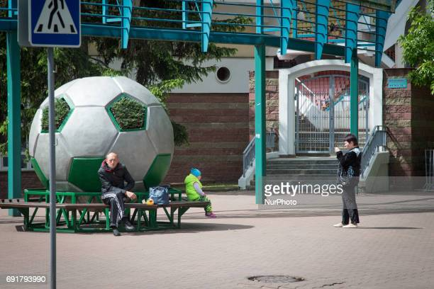 A woman is seen taking a photo with her phone at the entrance of the Brestsky sports complex the stadium where football club Dinamo Brest plays