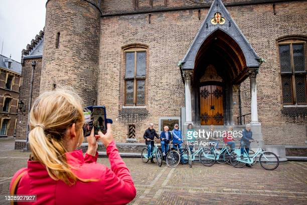 Woman is seen taking a picture of a group of people at the Binnenhof on July 15, 2021 in The Hague, Netherlands. The Binnenhof is closed due to a...
