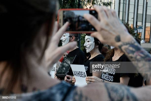 A woman is seen taking a picture of a protester wearing an anonymous mask during a demonstration by vegan activists for the 'voiceless' on Syntagma...