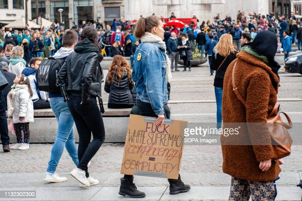 A woman is seen walking around the Dam square while holding a placard during the demonstration Thousands of people gathered at the Dam square in the...