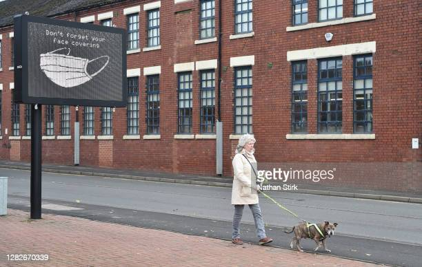 Woman is seen walking her dog next to a sign saying 'Don't forget your face covering' as Stoke-on-Trent prepares to move into Tier 2 COVID-19 on...