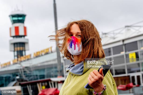 Woman is seen wearing a facemask while at the airport The first group of travelers depart from Rotterdam's The Hague airport with Transavia to...