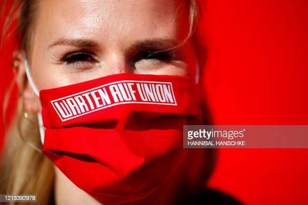 A woman is seen wearing a protective face mask with the inscription Waiting for Union prior to the German first division Bundesliga football match FC...