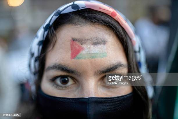 Woman is seen with a Palestinian flag painted on her face during the rally. Palestinians residing in Chile carry out a peaceful rally outside the...