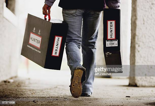 A woman is seen with pair of Hunter wellington boots at the factory shop on April 20 2006 in Dumfries ScotlandThe iconic wellington boot company...