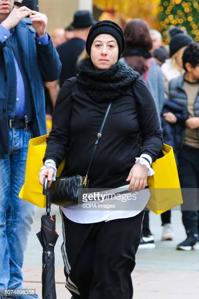 Woman is seen with Selfridges shopping bags on London's Oxford Street. Last minute Christmas shoppers take advantage of pre-Christmas bargains at...