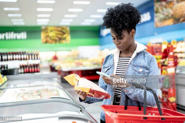 woman is shopping in supermarket and scanning barcode with smartphone - merchandise stock pictures, royalty-free photos & images