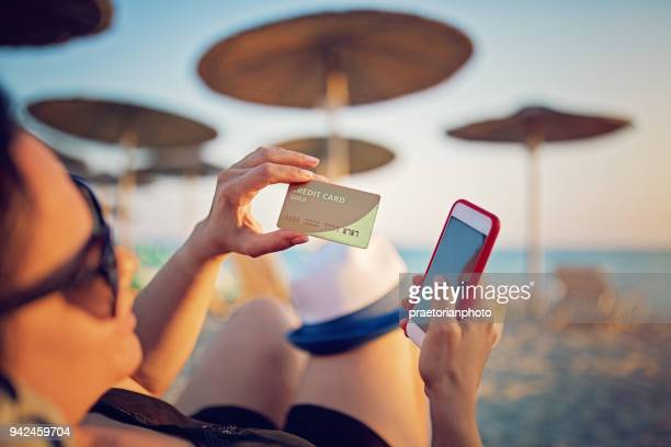woman is shopping online using her credit card on the beach - credit card stock pictures, royalty-free photos & images