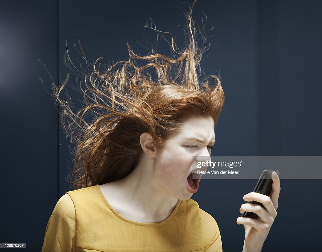 woman is shouting into phone. : Stock Photo