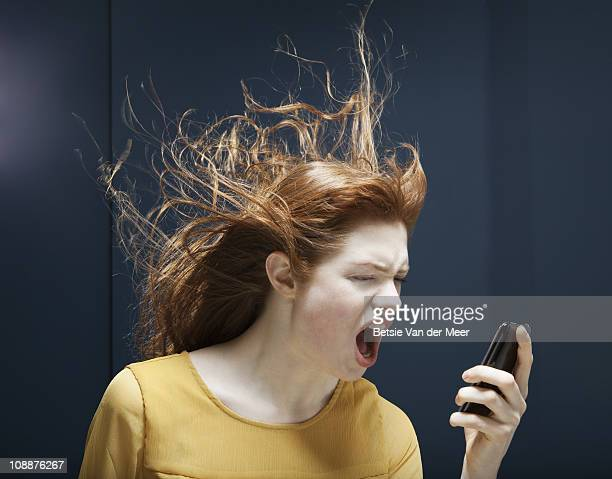 woman is shouting into phone. - furioso fotografías e imágenes de stock