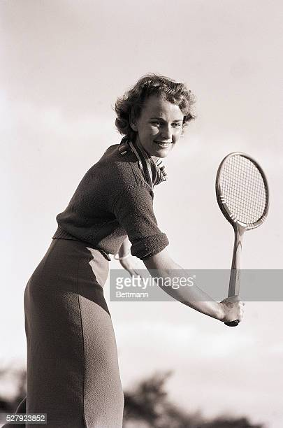 Woman is shown in midswing of a tennis racket Model Peggy Goldsmith 3/4 length photo Ca 1940s