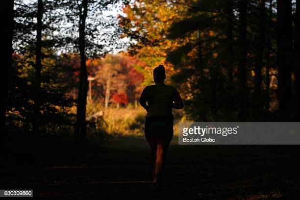 A woman is silhouetted against fall colors as she runs through White Memorial Conservation Center in Litchfield CT on Oct 7 2015