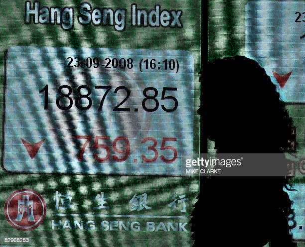 A woman is silhouetted as she walks past a board displaying the Hang Seng Index in Hong Kong on September 23 2008 Hong Kong shares closed down 39...