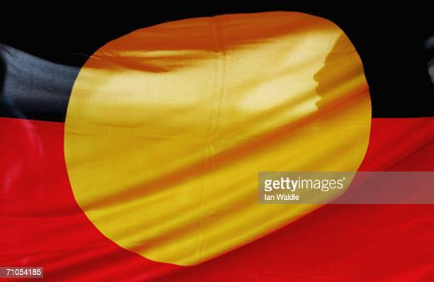 A woman is silhouetted behind the Aboriginal flag during an event to mark Sorry Day May 26 2006 in Sydney Australia The first National Sorry Day was...