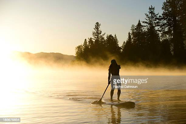 a woman, is silhouetted stand up paddleboarding (sup) at sunrise in the mist in lake tahoe, ca. - lake tahoe stock pictures, royalty-free photos & images