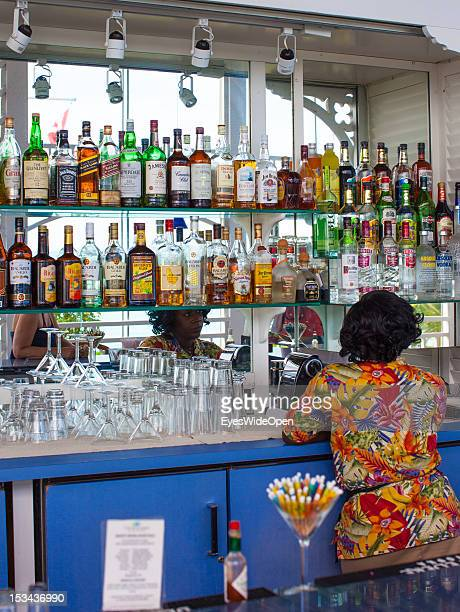 Woman is sitting at the bar of luxury Resort and Hotel Cape Santa Maria which is having one of the Bahamas´ best beaches with white sand and...