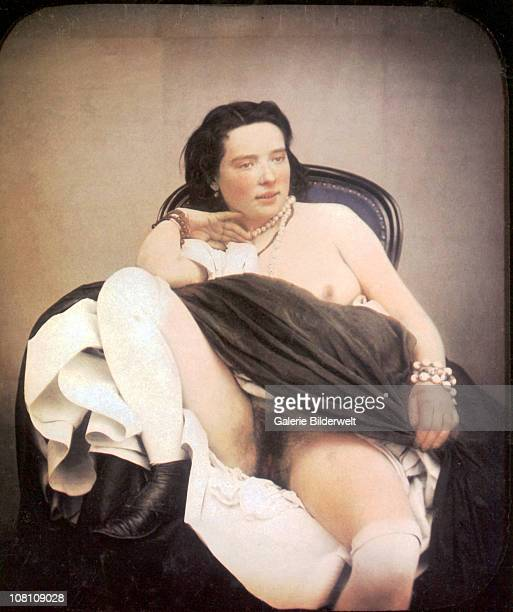 A woman is sitting in a chair with one breast as well as her thighs and vagina exposed wearing a pearl necklace 1850 Handcolored stereoscopic...