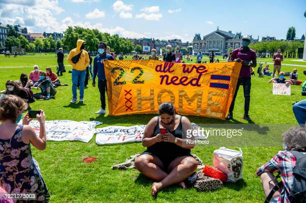 Woman is sitting in front of a big banner, during the Refugee Lives Matter demonstration in Amsterdam, Netherlands on June 20th, 2020.