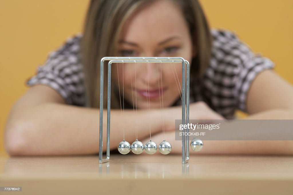 A woman is sitting in front of a shot-put pendulum : Photo