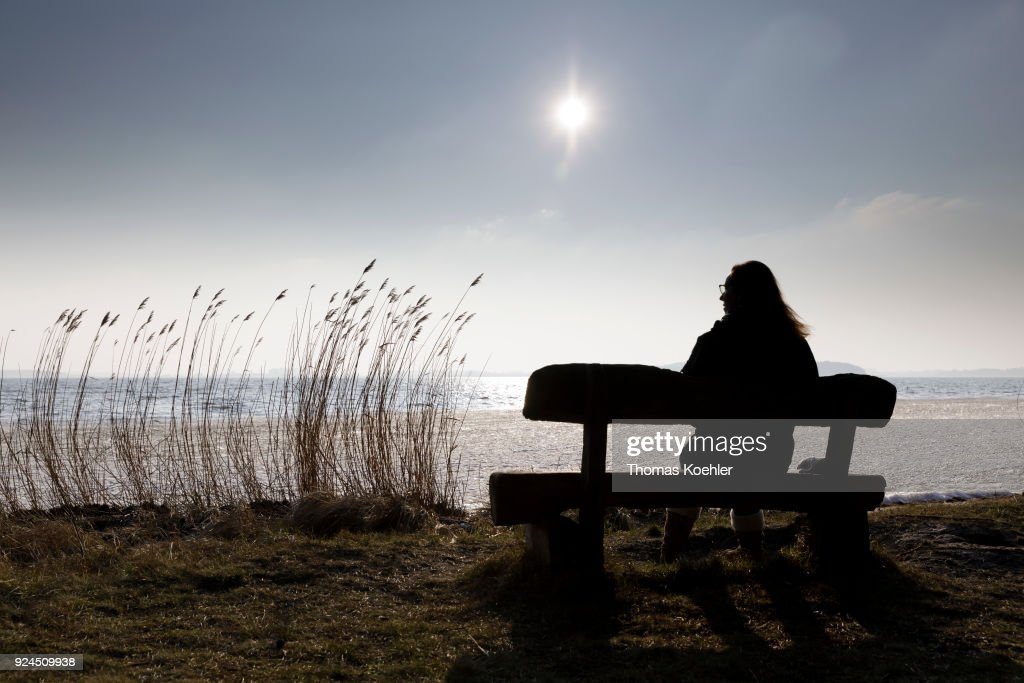 A woman is sitting on a bench at partially frozen Grosser Jasmunder Bodden near Glowe on the island Ruegen on February 09, 2018 in Glowe, Germany.