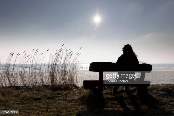 A woman is sitting on a bench at partially frozen Grosser Jasmunder Bodden near Glowe on the island Ruegen on February 09 2018 in Glowe Germany