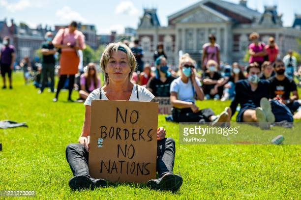 Woman is sitting on the grass, while holding a pro refugees placard, during the Refugee Lives Matter demonstration in Amsterdam, Netherlands on June...