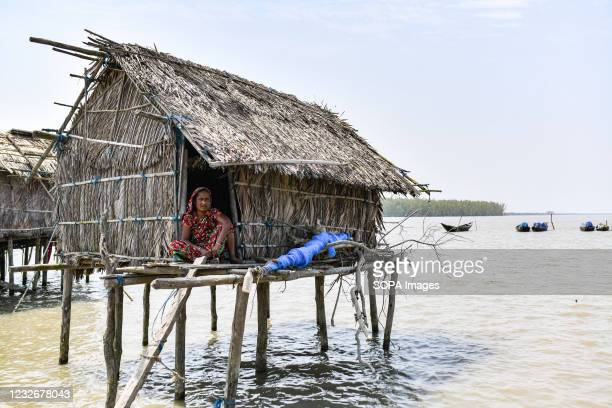 Woman is sitting outside her house at high tide, in a village next to the Sundarbans forest in Khulna.