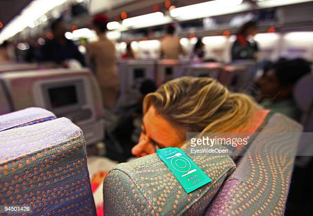 """Woman is sleeping in an aeroplane with a sticker on her seat """"Wake me up for lunch,dinner,breakfast"""" on board of a Emirates passenger jet. On..."""