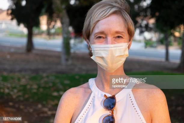 la femme sourit tout en portant un masque - une seule femme d'âge mûr photos et images de collection