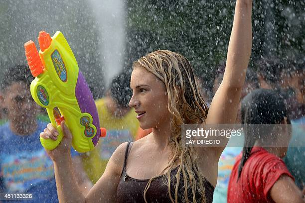 A woman is sprayed with water while holding a water pistol as residents celebrate the feast day of St John the Baptist in Manila on June 24 2014...