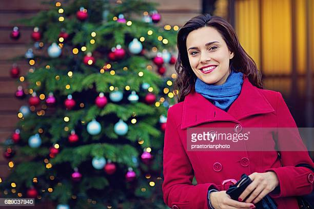 Woman is standing at the front of Cristmas tree