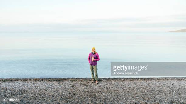 A woman is standing at the shore of Lake Taupo