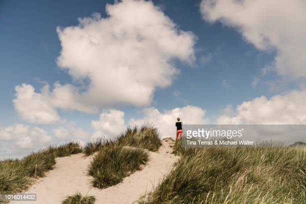 a woman is standing on a dune at the beach. sylt - german north sea region stock pictures, royalty-free photos & images