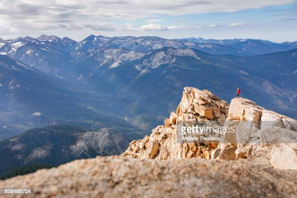 A woman is standing on a ridge on Alta Peak in Sequoia National Park.