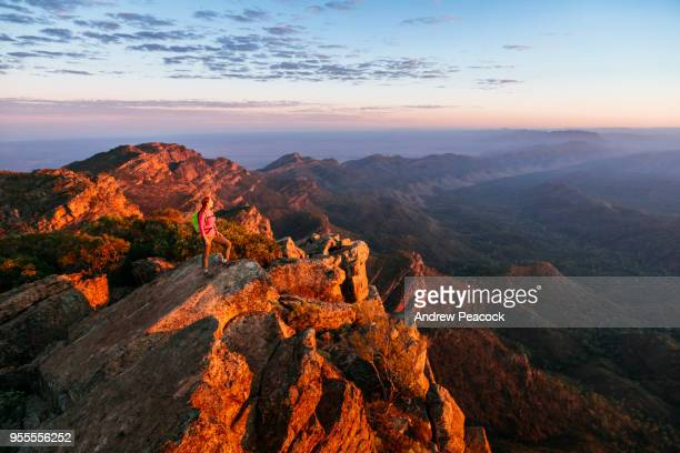 a woman is standing on st mary peak at sunrise, the highest point in the flinders ranges national park, south australia - south australia stock pictures, royalty-free photos & images