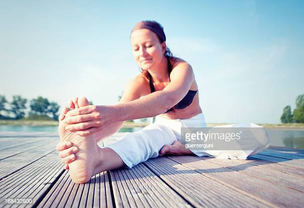 Woman is stretching her legs on a dock