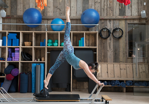Woman is stretching on a reformer in pilates studio. - gettyimageskorea