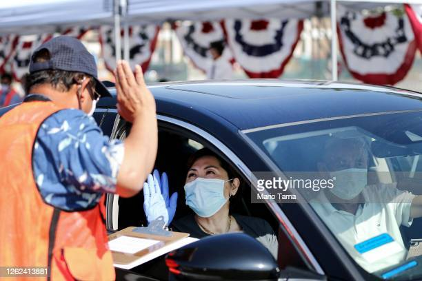 Woman is sworn in as a new U.S. Citizen from inside a vehicle at a drive-in naturalization ceremony conducted amid the COVID-19 pandemic on July 29,...