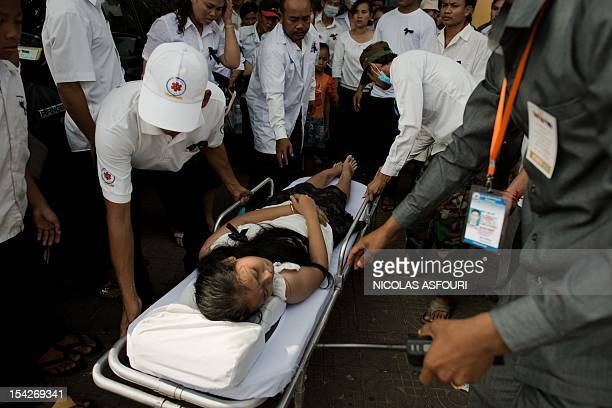 A woman is taken away by medics on a stretcher after she fainted from fatigue as she waited for the convoy transporting the coffin of late former...