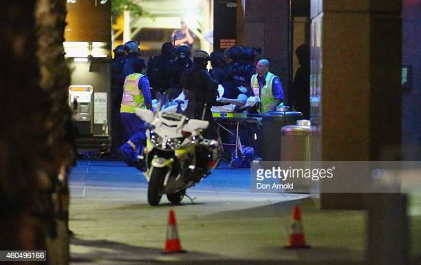 A woman is taken to an ambulance by stretcher outside Lindt Cafe Martin Place on December 15 2014 in Sydney Australia Police attend a hostage...