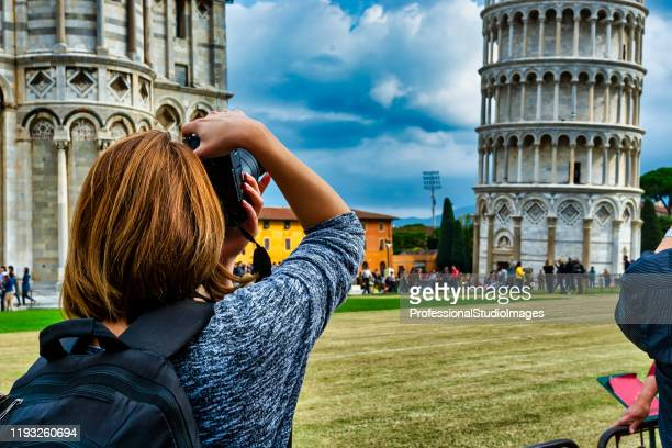 a woman is taking a photo of leaning tower of pisa - pisa stock pictures, royalty-free photos & images