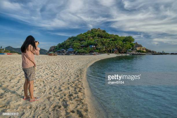 A woman is taking photo of a beautiful beach and island at Nang Yuan Island, Thailand.