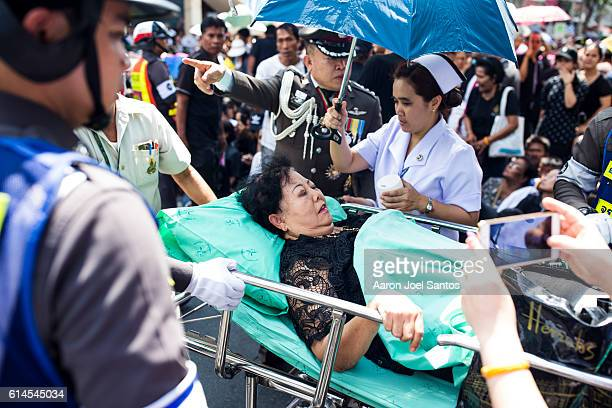 A woman is treated for heatstroke while awaiting the funeral procession of King Bhumibol on October 14 2016 in Bangkok Thailand Thailand's King...